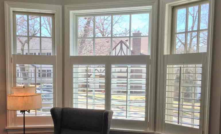 Half plantation shutters in family room bay window.