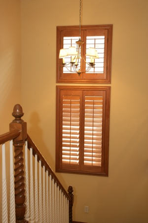 Wooden shutters in tan stairwell.
