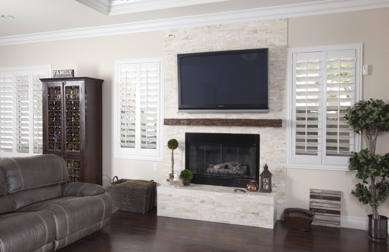 White plantation shutters in a Atlanta living room with plank hardwood floors.