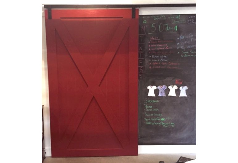 Red barn door with black track next to chalkboard