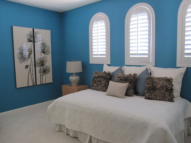Bedroom with arched white shutters.