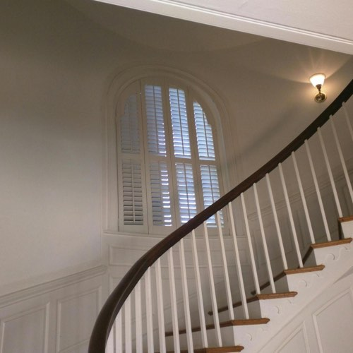White plantation shutters decorating arched window located in round stairwell.