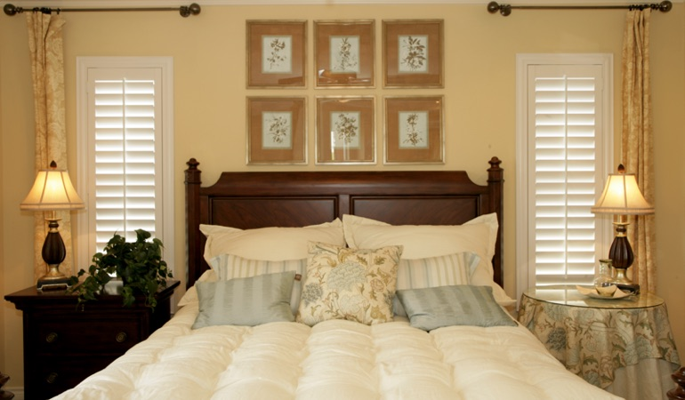 Beige bedroom with white plantation shutters covering windows in Atlanta