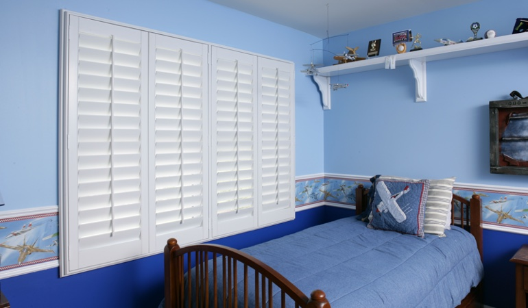Large plantation shutters covering window in blue kids bedroom in Atlanta